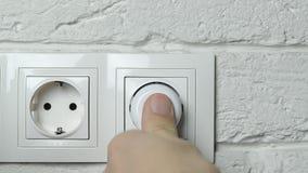 Primer de la mano de un hombre que inserta un enchufe eléctrico en un socket de pared almacen de metraje de vídeo