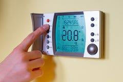 Primer de la mano de una mujer que fija la temperatura ambiente en un modo Fotos de archivo libres de regalías