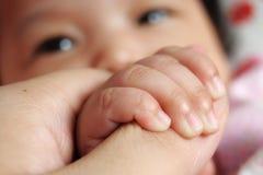 Primer de la mano del bebé con los ojos Fotografía de archivo libre de regalías