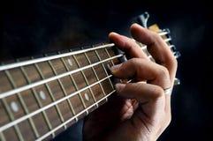 Primer de la mano del guitarrista que toca la guitarra Foto de archivo libre de regalías