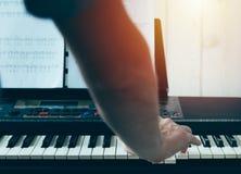 Primer de la mano del hombre de un ejecutante de la música que juega el piano de la parte posterior foto de archivo libre de regalías