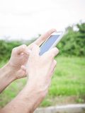 Primer de la mano del hombre usando un teléfono elegante Fotografía de archivo libre de regalías