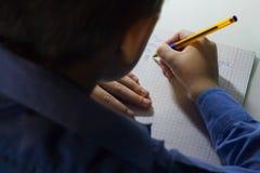 Primer de la mano del muchacho con el lápiz que escribe palabras inglesas a mano en el papel blanco tradicional de la libreta Foto de archivo libre de regalías