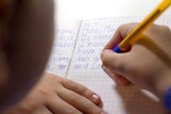 Primer de la mano del muchacho con el lápiz que escribe palabras inglesas a mano en el papel blanco tradicional de la libreta Imágenes de archivo libres de regalías