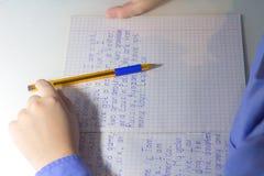 Primer de la mano del muchacho con el lápiz que escribe palabras inglesas a mano en el papel blanco tradicional de la libreta Imagen de archivo libre de regalías