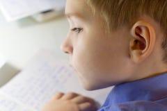Primer de la mano del muchacho con el lápiz que escribe palabras inglesas a mano en el papel blanco tradicional de la libreta Fotografía de archivo