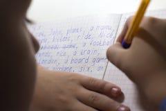 Primer de la mano del muchacho con el lápiz que escribe palabras inglesas a mano en el papel blanco tradicional de la libreta Foto de archivo