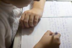 Primer de la mano del muchacho con el lápiz que escribe palabras inglesas a mano en el papel blanco tradicional de la libreta Imagenes de archivo