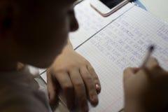 Primer de la mano del muchacho con el lápiz que escribe palabras inglesas a mano en el papel blanco tradicional de la libreta Fotos de archivo