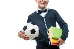 Primer de la mano del ` s del colegial con la bola y los libros de texto, colegial Fotografía de archivo libre de regalías