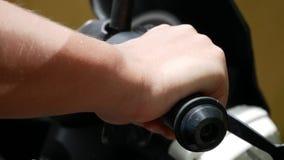 Primer de la mano del ` s del hombre en los manillares de la motocicleta almacen de video