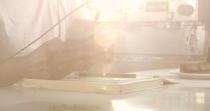 Primer de la mano del ` s del hombre usando un smartphone y del dibujo en café almacen de video