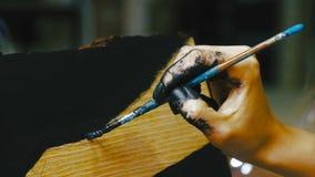 Primer de la mano del ` s de la mujer del artista con el cepillo todavía que pinta la imagen de la vida en lona en estudio del ar almacen de metraje de vídeo