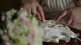 Primer de la mano del ` s de la novia que ata los anillos de bodas a un cojín hermoso almacen de metraje de vídeo