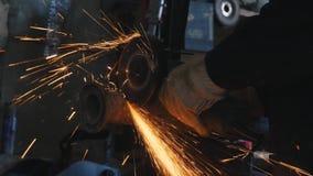 Primer de la mano del trabajador, llevando en los guantes protectores, cortando el tubo del metal Capítulo Trabajo peligroso con  almacen de video