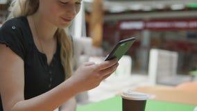 Primer de la mano femenina con smartphone a disposición en el fondo de la tabla del café metrajes