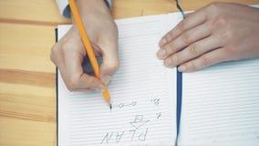 Primer de la mano femenina que anota estrategia en cuaderno con el lápiz Empresaria que compone el nuevo plan empresarial almacen de video