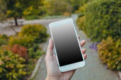 Primer de la mano femenina usando un teléfono elegante fotos de archivo