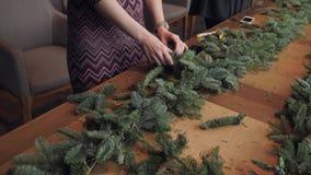 Primer de la mano Florista en el trabajo: la mujer da la fabricación de la guirnalda de las decoraciones de la Navidad del abeto  metrajes