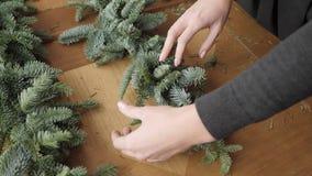 Primer de la mano Florista en el trabajo: la mujer da la fabricación de la guirnalda de las decoraciones de la Navidad del abeto  almacen de video