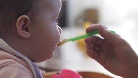 Primer de la mano de la madre juguetón alimentando su babero que lleva de la pequeña hija linda linda almacen de metraje de vídeo
