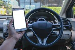 Primer de la mano masculina del conductor usando smartphone en coche el día soleado foto de archivo