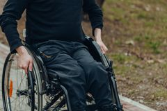 Primer de la mano masculina en la rueda de la silla de ruedas durante paseo en parque fotos de archivo libres de regalías