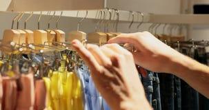 Primer de la mano masculina que coge la ropa en boutique almacen de metraje de vídeo