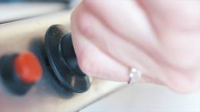 Primer de la mano de la mujer joven con el gas de torneado del anillo hermoso apagado de una estufa de gas de la cocina acci?n Pr imágenes de archivo libres de regalías