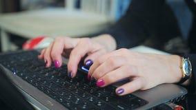 Primer de la mano de la mujer de negocios que mecanografía en el teclado del ordenador portátil almacen de metraje de vídeo