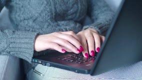 Primer de la mano de la mujer de negocios que mecanografía en el teclado del ordenador portátil El primer de una hembra da mecano metrajes