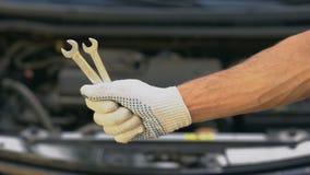 Primer de la mano que detiene a las llaves inglesas, reparando el coche en el garaje, actualizando el vehículo almacen de video