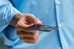 Primer de la mano que sostiene y que da la tarjeta de crédito para el pago Imagen de archivo