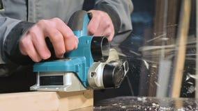 Primer de la mano de un carpintero que trabaja con un avión eléctrico en un taller casero Partes de madera de acabado en la cámar almacen de metraje de vídeo
