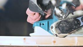 Primer de la mano de un carpintero que trabaja con un avión eléctrico en un taller casero Partes de madera de acabado en la cámar metrajes