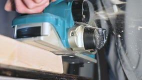Primer de la mano de un carpintero que trabaja con un avión eléctrico en un taller casero Partes de madera de acabado en la cámar almacen de video