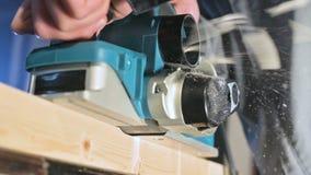 Primer de la mano de un carpintero que trabaja con un avi?n el?ctrico en un taller casero Partes de madera de acabado en la c?mar almacen de video