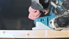 Primer de la mano de un carpintero que trabaja con un avi?n el?ctrico en un taller casero Partes de madera de acabado en la c?mar metrajes