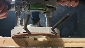 Primer de la mano de un carpintero que trabaja con un cortador eléctrico manual en un taller casero Partes de madera de acabado e metrajes