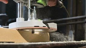 Primer de la mano de un carpintero que trabaja con un cortador eléctrico manual en un taller casero Partes de madera de acabado e almacen de video