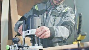 Primer de la mano de un carpintero que trabaja con un cortador eléctrico manual en un taller casero Piezas de madera de acabado almacen de video