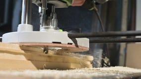 Primer de la mano de un carpintero que trabaja con un cortador el?ctrico manual en un taller casero Partes de madera de acabado e metrajes