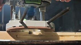 Primer de la mano de un carpintero que trabaja con un cortador el?ctrico manual en un taller casero Partes de madera de acabado e almacen de video