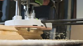Primer de la mano de un carpintero que trabaja con un cortador el?ctrico manual en un taller casero Partes de madera de acabado e almacen de metraje de vídeo