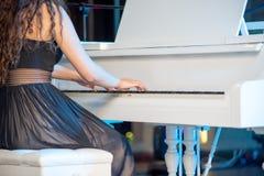 Primer de la mano de un ejecutante de la música que juega el piano imagen de archivo