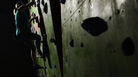 Primer de la mano de un escalador de la mujer que sube en la pared que sube a lo largo de la pared que dispara para las competenc almacen de video