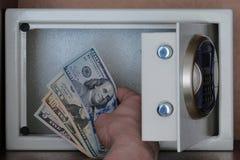 Primer de la mano de un hombre que pone dólares americanos en una caja de depósito seguro Billetes de banco de 5, 10, 20, 100 dól imágenes de archivo libres de regalías