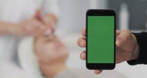 Primer de la mano de un hombre que sostiene smartphone verde de la pantalla en el fondo de los procedimientos del osmetology El o almacen de video