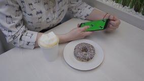 Primer de la mano de una mujer joven que sostiene una pantalla del verde del teléfono móvil En la tabla es un buñuelo y un café almacen de metraje de vídeo