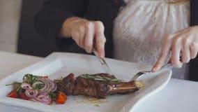 Primer de la mano de una mujer que, con la ayuda de un cuchillo y de una bifurcación, come el filete asado en un restaurante almacen de video